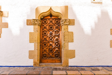 The wooden door of the museum Marisel de Mar, Sitges, Barcelona, Catalunya, Spain. Ñopy space for text.