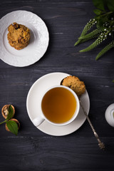Herbal tea and homemade oatmeal nut cookies on a dark wooden background. Top view