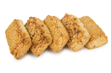 Row of shortbreads with nuts and sesame isolated on white