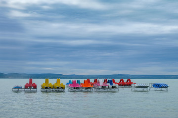 colorful paddle boats at Balaton lake waiting for summer season - over water, cloudy and windy weather, ready for holiday
