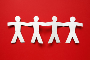 chain of paper people on red background