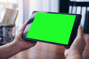 Mockup image of hands holding black tablet pc with white blank green screen on wooden table background in coffee shop