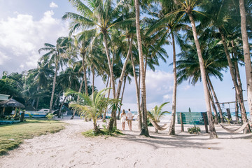Young couple look to the sea,the fresh green palm trees around. They stand on the white sand with a tropical sea and blue sky with clouds on the background.