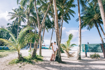 Young couple embrace each other near the fresh green palm tree. They are happy. They stand on the white sand with a tropical sea and blue sky with clouds on the background.