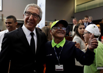 Diniz, the third largest Carrefour shareholder, poses for a photo with an employee during the company's IPO at Sao Paulo's stock exchange in Sao Paulo