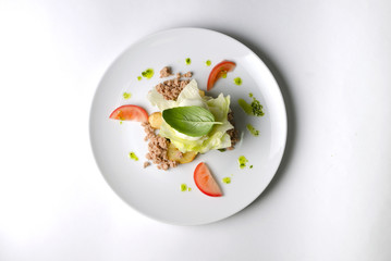 Mix salad with egg poached and tuna on a white plate