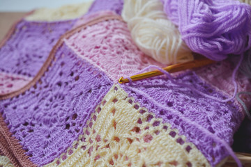 Selective focus crochet hook on vintage crochet pattern and colorful yarn