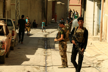 Members of the Counter Terrorism Service (CTS) patrol on foot in West Mosul, Iraq