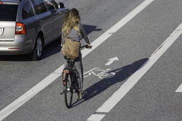 Frau mit Tasche auf Radstreifen