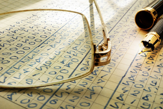 Audit trail. Glasses, pen and accounting ledger. Selective focus.
