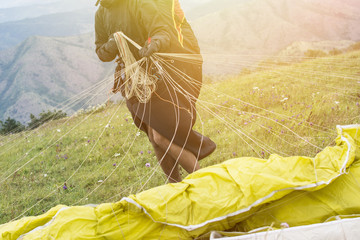 Close up of a paraglider on a mountain top packing his parachute. Flying over a mountain valley in summer sunny day. Extreme sport.