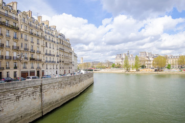 Seine River in Paris with the City Hall on the back and generic old historic parisian buildings on the front on a sunny spring day in this beautiful European city