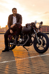 Handsome rider man with beard and mustache in black leather biker jacket sit on classic style cafe racer motorcycle at sunset time. Bike custom made in vintage garage. Brutal fun urban lifestyle.