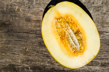 Half of melon on rustic wooden background