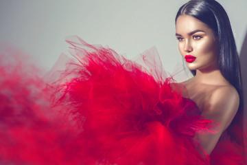 Obraz Gorgeous brunette model woman in red dress posing in studio - fototapety do salonu