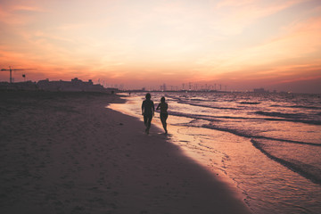 Romantic couple silhouette by ocean at sunset.  Romantic couple walks towards sunset holding hands