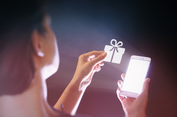Image of a woman with a smartphone in her  hand. She gets a gift. Concept of gift in the age of digital technology.