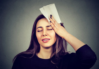 woman wipes sweat from her forehead with a handkerchief
