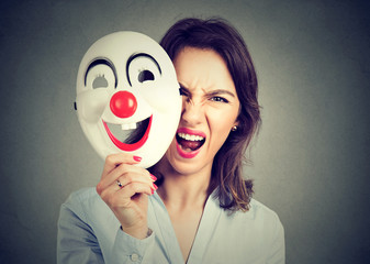 angry screaming woman taking off happy clown mask