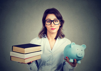 woman with stack of books and piggy bank full of debt rethinking career path