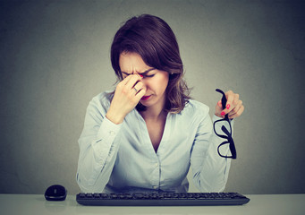 Woman with glasses having eyestrain after long hours working on computer