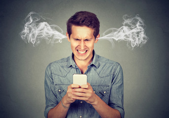 Angry man reading a text message on smartphone blowing steam coming out of ears