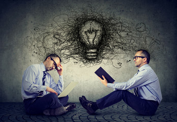 Businessmen sitting on a floor in office one using laptop another reading a book with light bulb and idea thoughts in-between