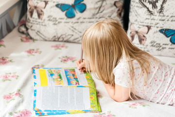 Cute liitle blonde girl lying on a bed and making hometasks in the workbook with a pencil in a hand.