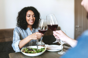 Beautiful African American girl having dinner with friend in restaurant. Young smiling lady with dark curly hair eating salad and drinking red wine with friend at cafe