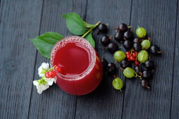 Fruit juice and berries on wooden background