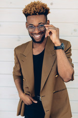 A portrait of African American man in jacket and glasses with smartphone standing near the wooden wall