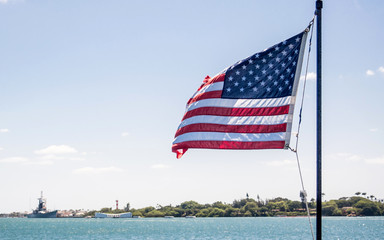An America flag is flying on the background of Pearl Harbor
