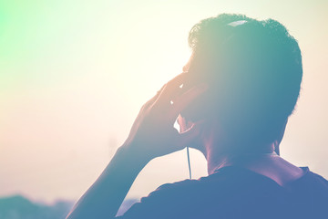 Man silhouette listening to the headphones on the sunset landscape background, Soft and sweet tone