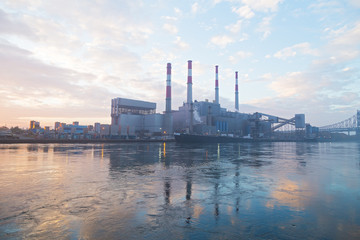 New York city infrastructure on the shore of East River at dawn. Electric Power plant before sunrise on a foggy morning.