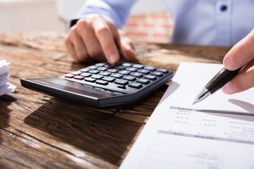 Person Calculating Finance Using Calculator