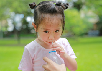 Close Up little girl drinking water in the park. Portrait outdoor.