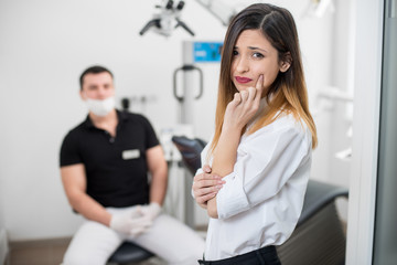 Young woman suffering from terrible teeth pain, touching cheek with hand at dental clinic. Female feeling toothache. On the background dentist sitting on the chair. Dental care and health concept