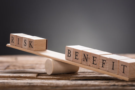 Closeup Of Risk And Benefit Wooden Blocks On Seesaw