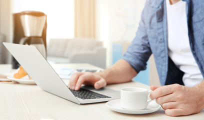 Young man sitting at table with laptop and cup of coffee