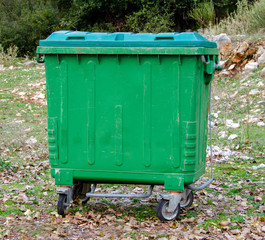 Metal green garbage can with wheels in countryside