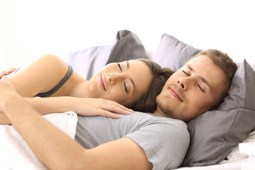 Happy couple sleeping together on a bed