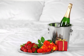 Romantic composition with champagne and strawberry on bed. Honeymoon concept