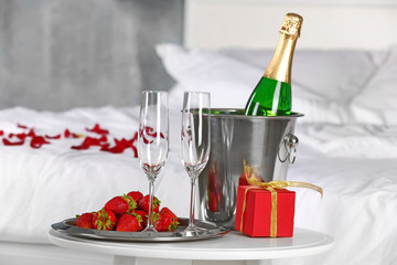 Romantic composition with champagne and strawberry on table in bedroom. Honeymoon concept