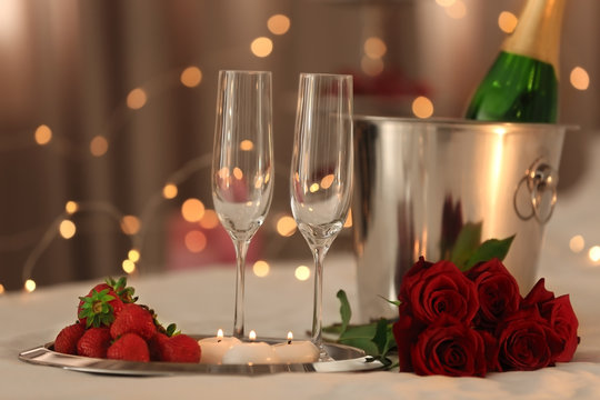 Romantic composition with champagne and strawberry on blurred background. Honeymoon concept