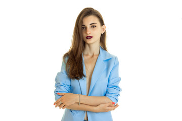 Cute business girl in blue jacket without bra looking at the camera