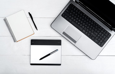 Top view on white wooden table with open blank laptop computer, empty diary and graphic tablet, free space