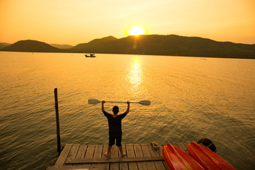 The boy start rowing oars in sae of kayak at early evening. Golden sunset.Summer time, active recreation. Healthy lifestyle and care about mental health, resting in privacy and peace.