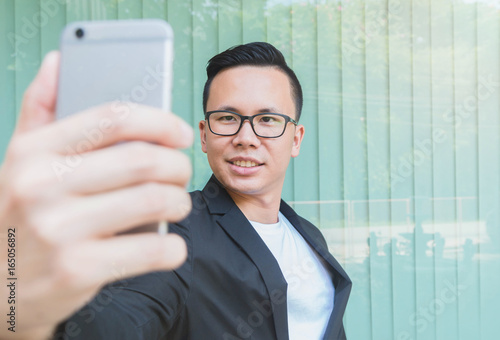 Happy Asian Businessman Making Video Call With Smartphone At The