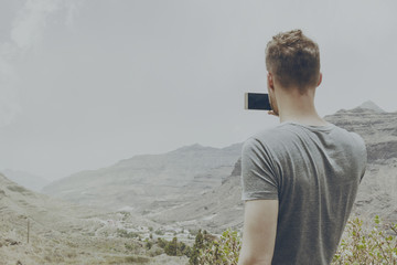 Young attractive man making picture of nature landscape with his smartphone. Toning.