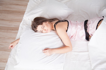 beautiful girl in pajamas asleep on a bed with linen
